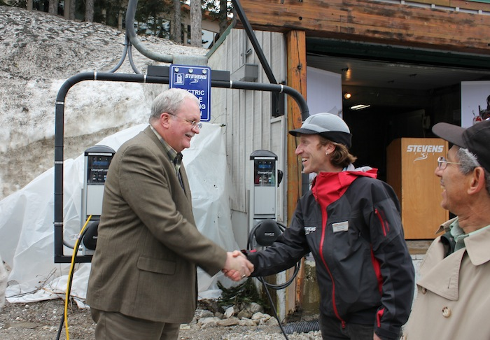 Washington 12th District Representative Mike Armstrong (L) shakes hands with Ross Freeman (R), Stevens Pass Environmental and Sustainability Manager, as Ron Johnston-Rodriguez, Economic Development Director for the Port of Chelan County looks on during the opening of two electric car charging stations at the ski resort.