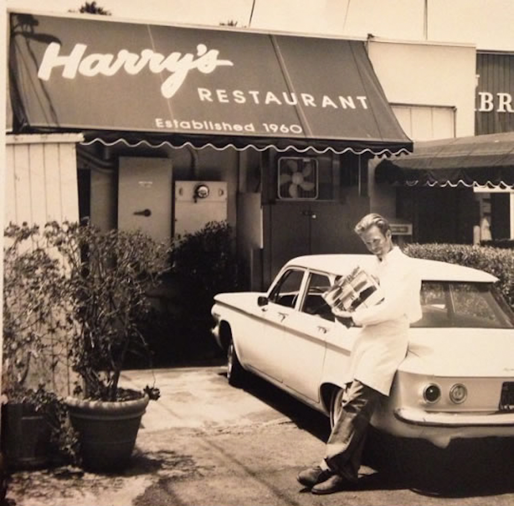Harry III poses with a customer's classic Corvair in front of the shop.