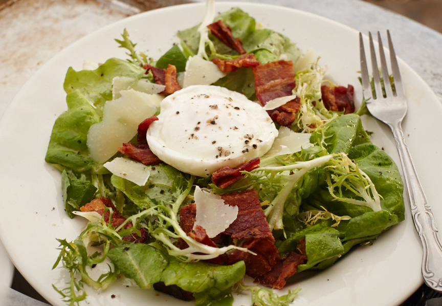 Frisée and Bibb lettuce salad with a poached egg, bacon, croutons, shaved parmesan and warmed sherry vinaigrette.