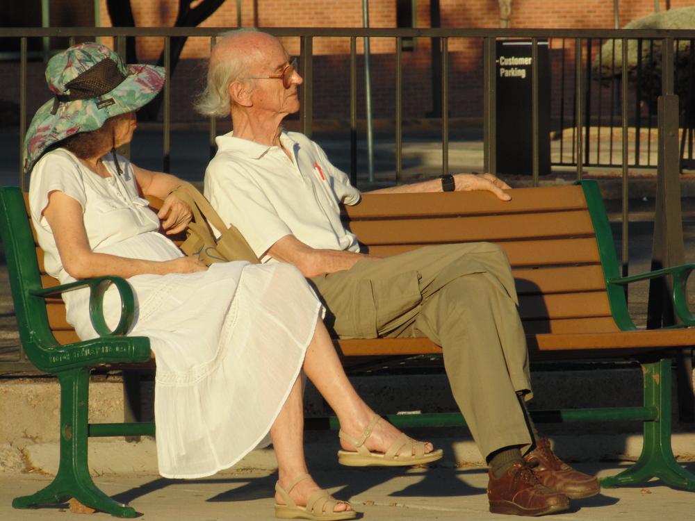 Paseantes con ropa de Domingo esperan el autobús sobre la Calle Oregon Norte, El Paso, Texas.