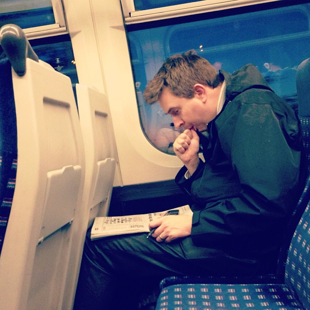 Passing time… Things people do in trains… #trains #photography #commuters #people #crosswords #london