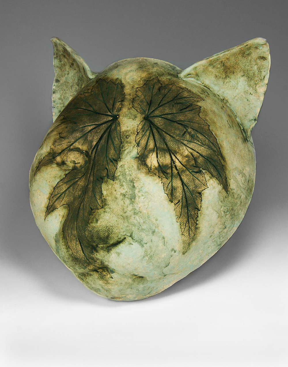 linda william's green cat face planter professionally photographed by john higby of eugene oregon on a gradient background