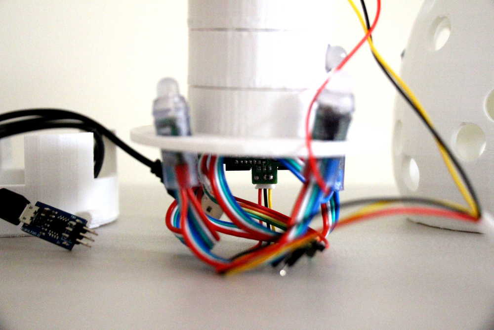 The cables, including the micro-USB power plug, are tucked into the base.