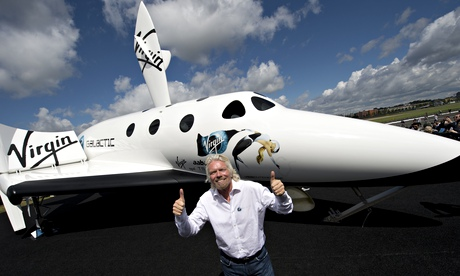 Richard Branson posing exuberantly in front of a model of Virgin Galactic's White Knight space plane