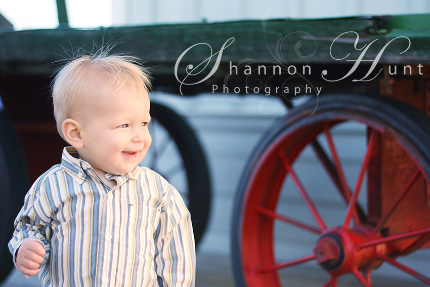 Toddler Portrait Photography, child and a wagon wheel captured by toddler photographer in Frisco, Texas