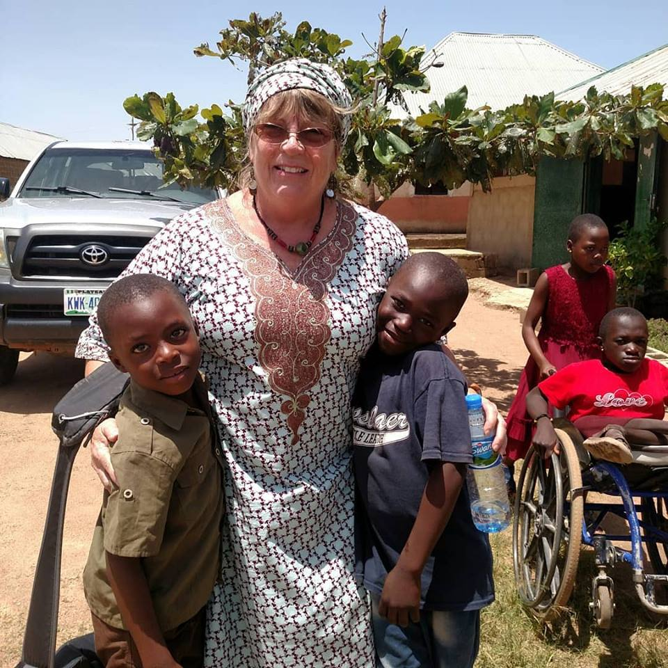Miss Paula loving the children in her Nigerian outfit