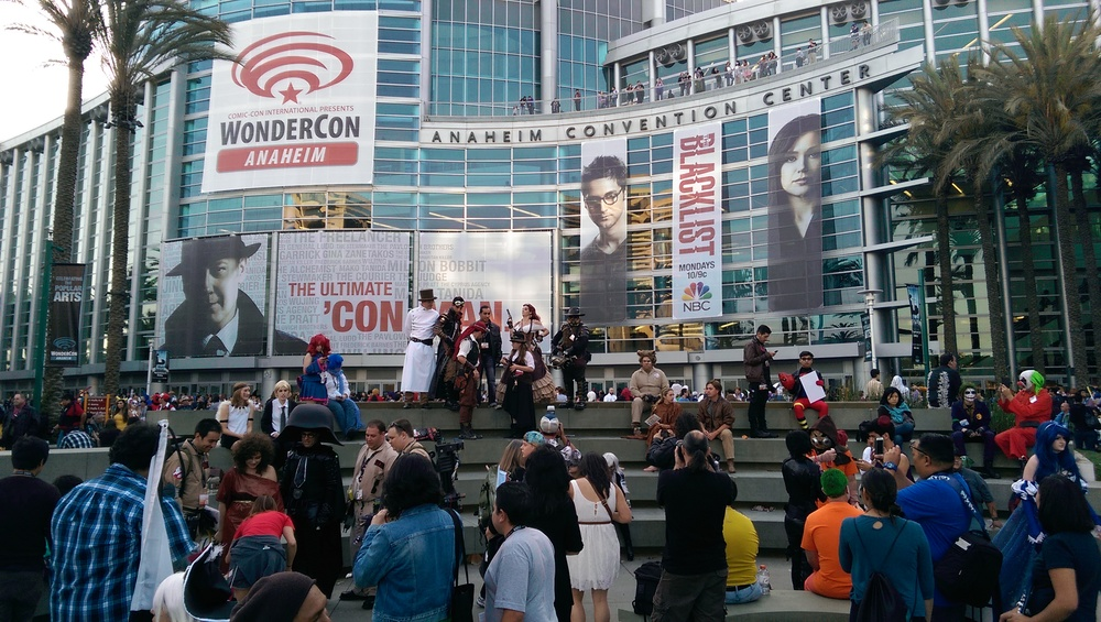 Cosplayers, attendees, and passerbys mingling outside the convention center during WonderCon