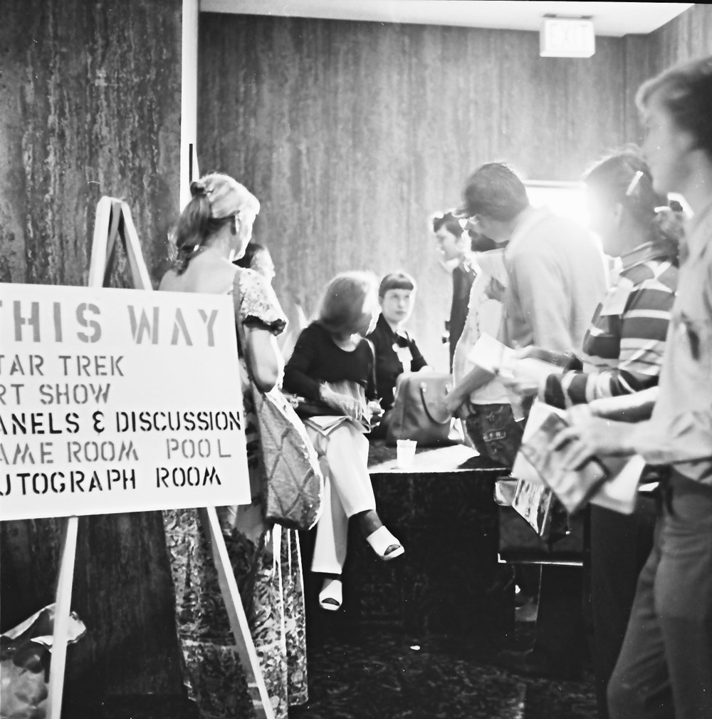 Sign directing attendees to some of of the exhibits and activities of the 1973 San Diego Comic-Con. Also notice, that about half of the people pictured are women.