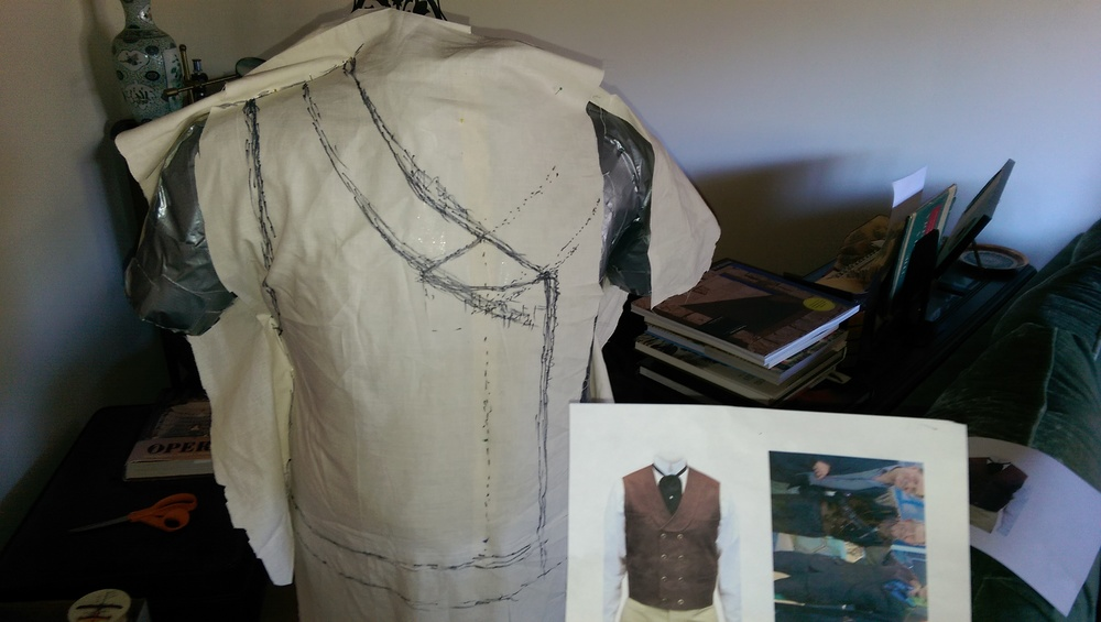 Marking the shape of the waistcoat on muslin that's draped and pinned over the body forrm