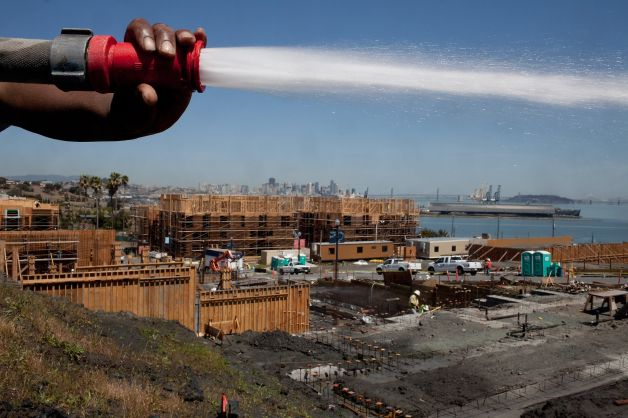 Michael Brown sprays down the land at the Shipyard, the new development at Hunters Point in San Francisco. Photo: Tim Hussin, Special To The Chronicle