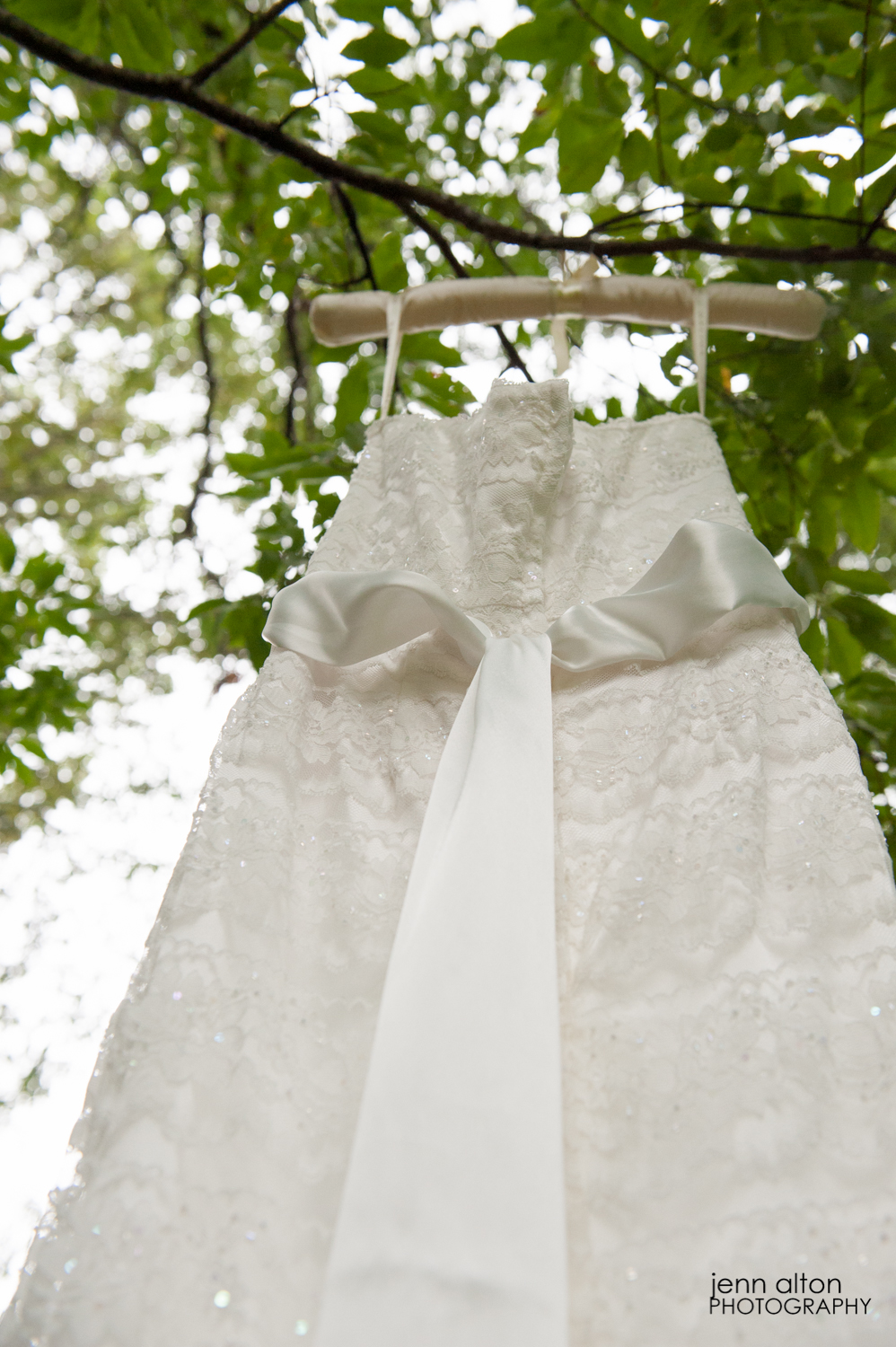 Wedding gown details displayed in a green leafy tree.