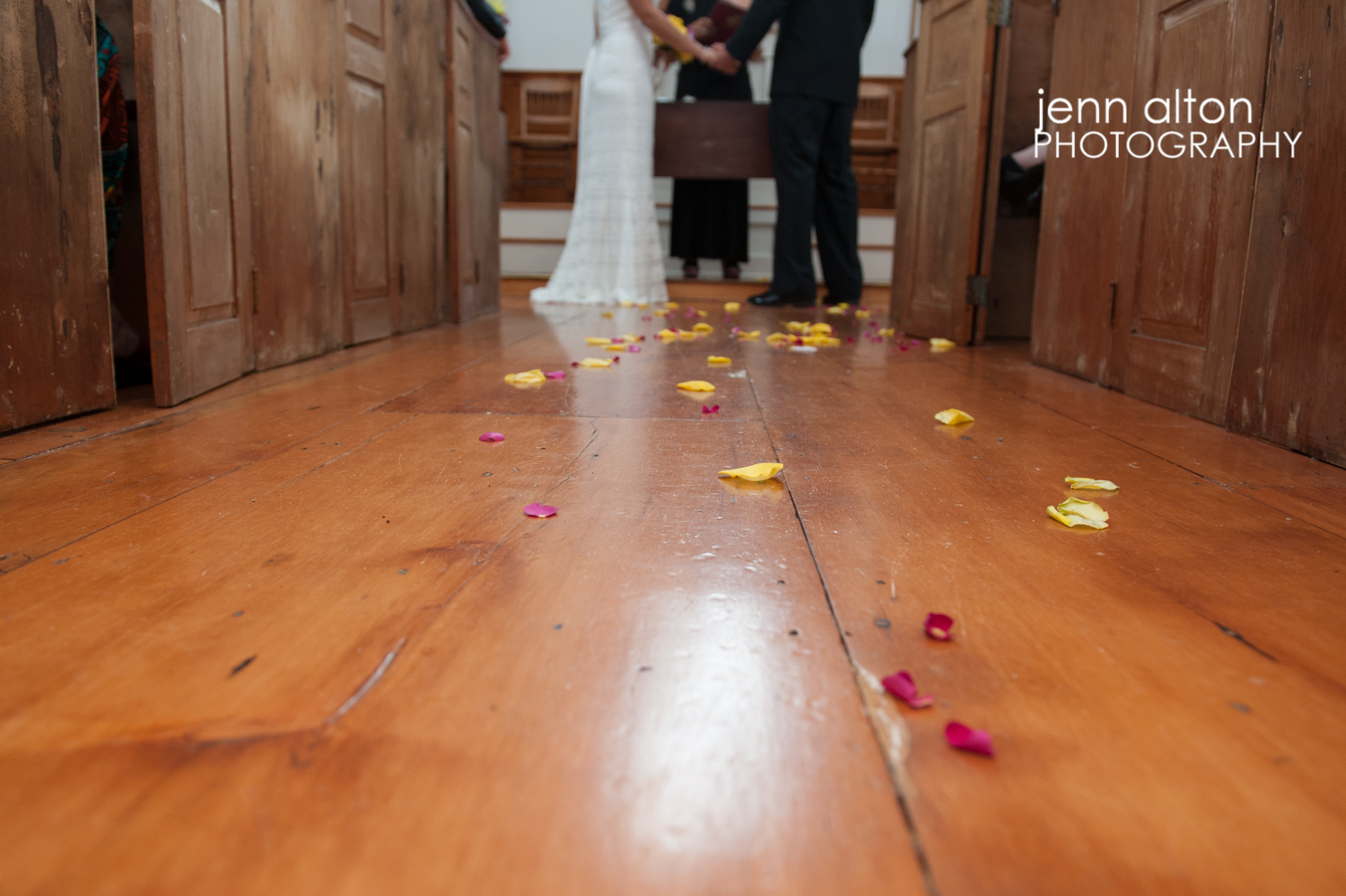 Bride and groom holding hands during ceremony and flower petals on the floor, Mashpee Old Indian Meeting House