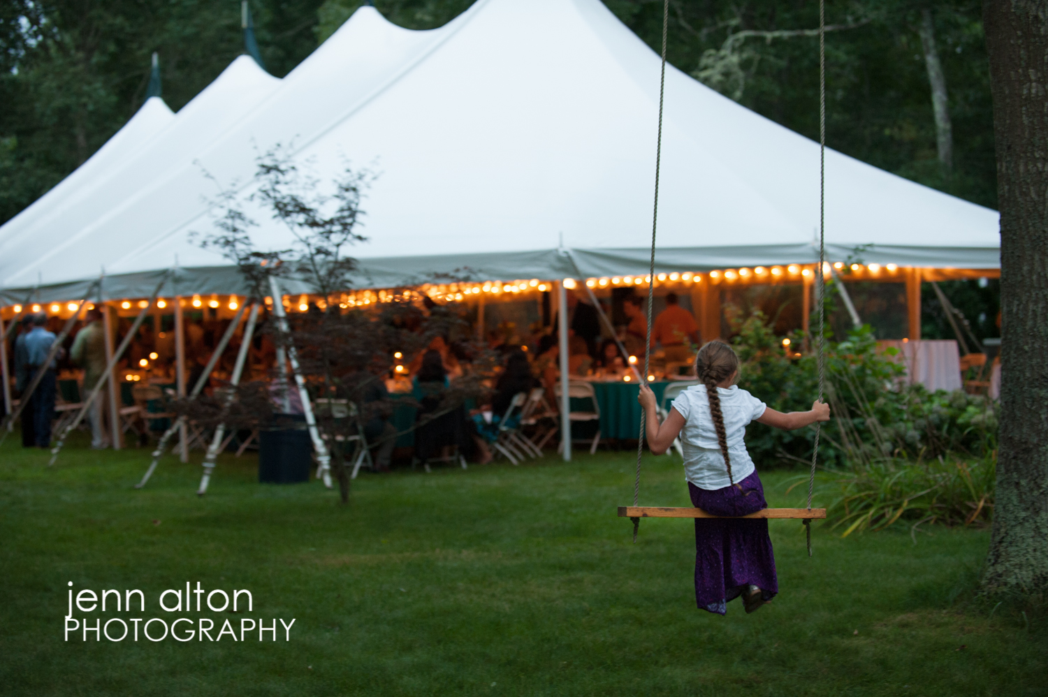 Tent reception and child on swing looking on, Cape Cod Wedding