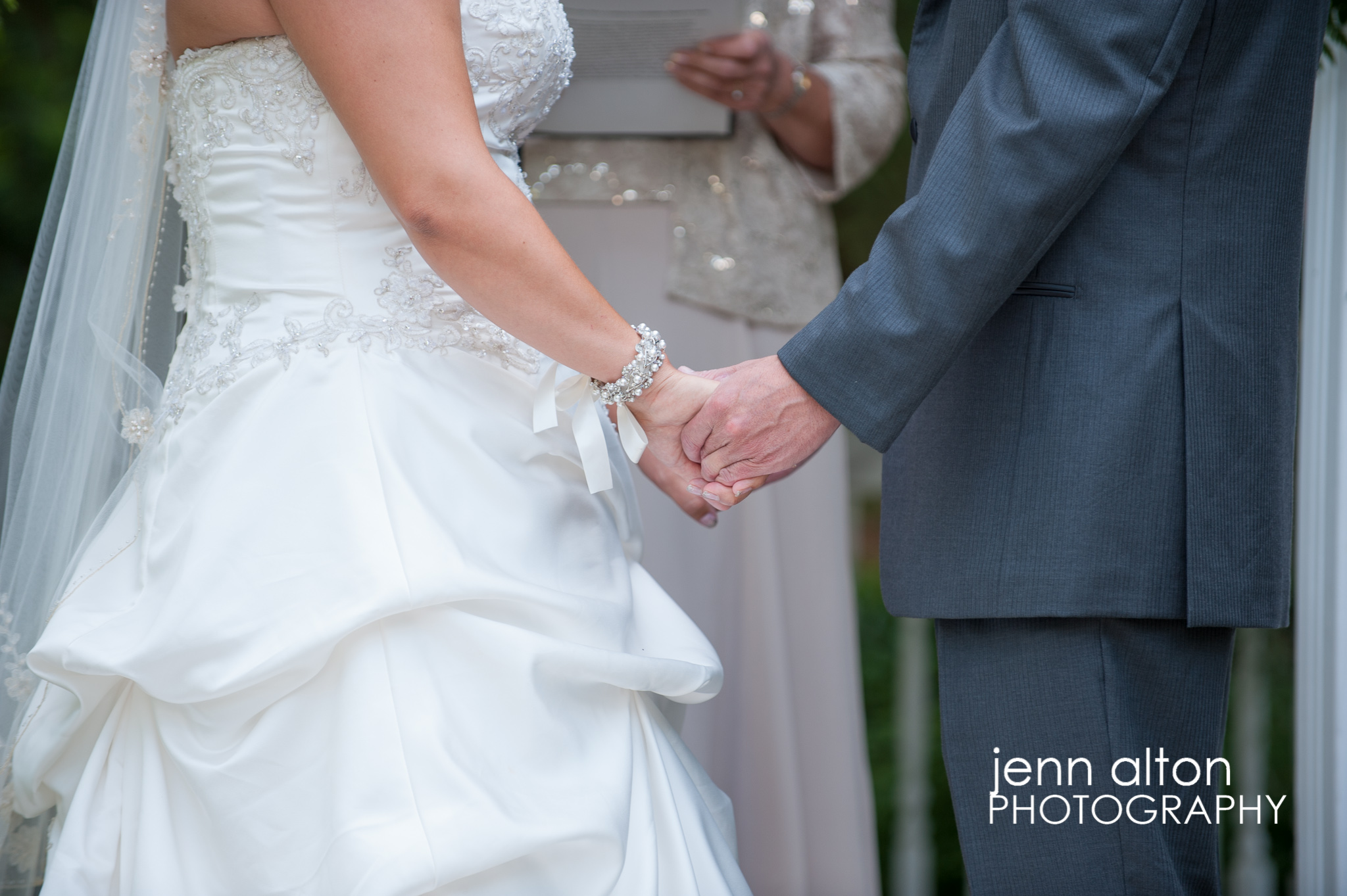 Bride and groom holding hands during ceremony, Pinehills Golf Club Ceremony