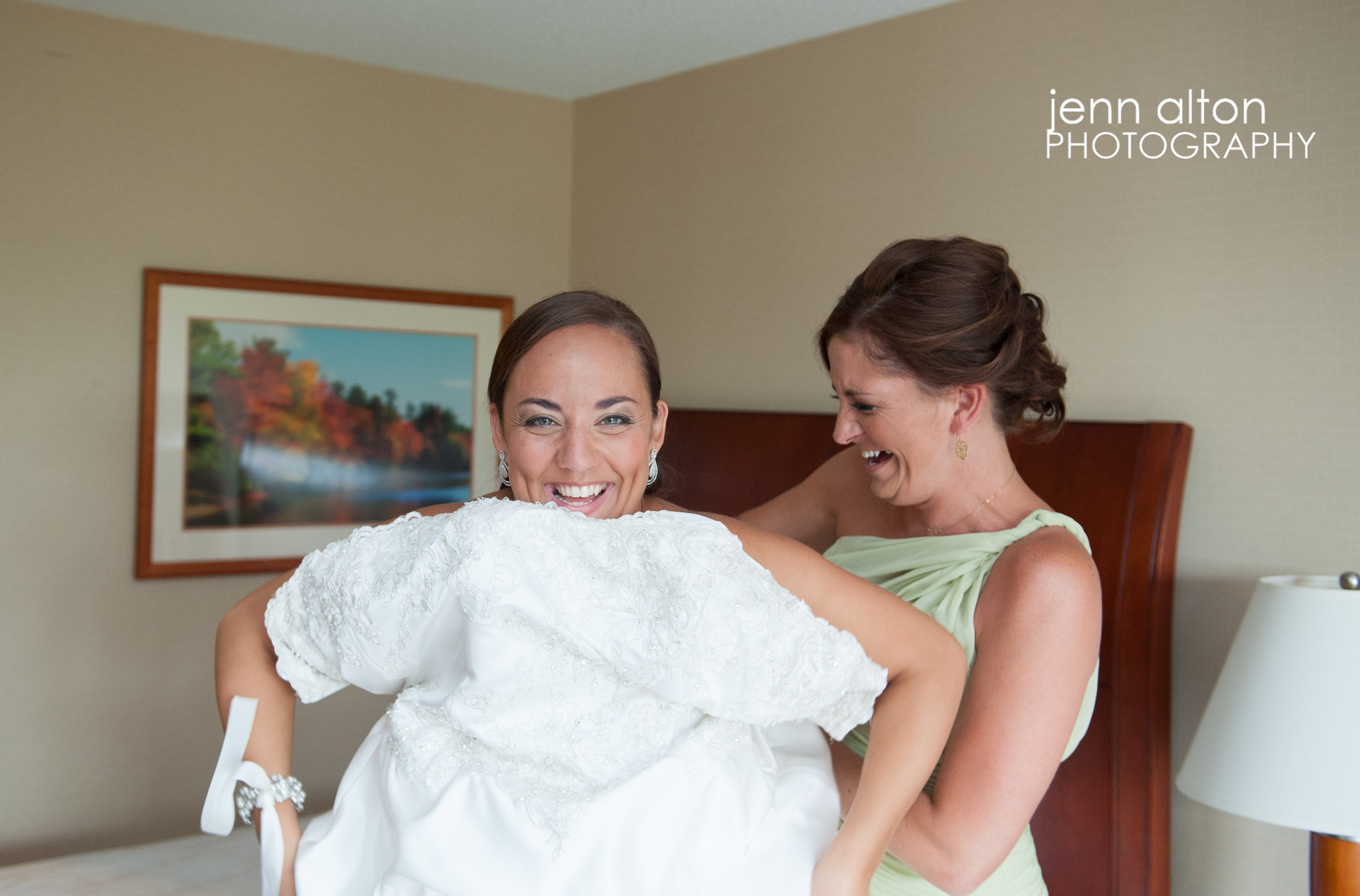 Bride and maid of honor getting into dress
