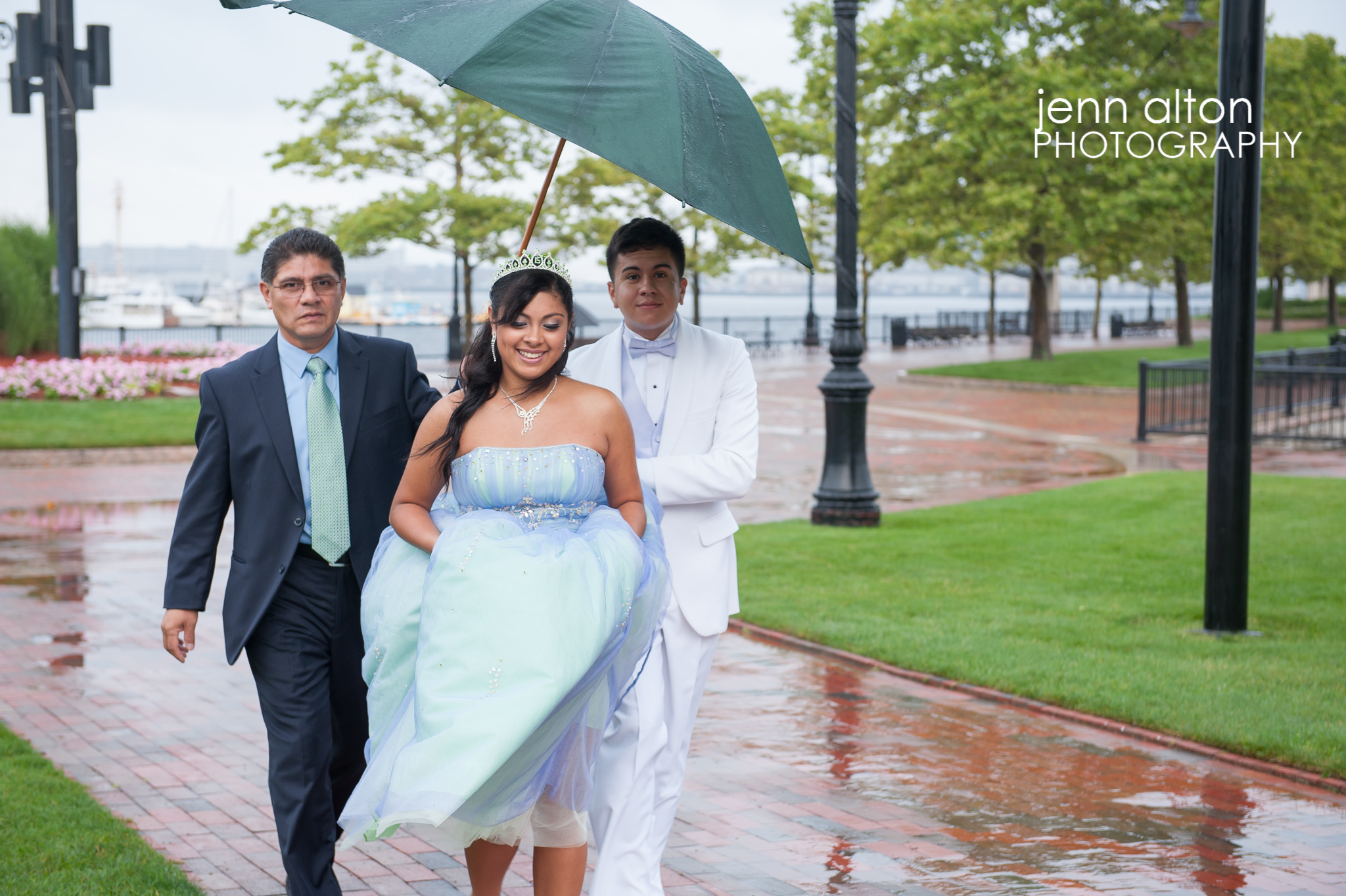 Quinceanera, father and Chambelan under umbrella at park, East Boston