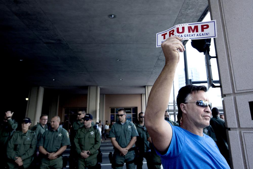 En Trump-supporter utanför Tampa Convention Center där Donald Trump höll ett valmöte dagen före primärvalet i Florida. Många poliser var även på plats i fall det skulle bli bråk mellan anti Trump-demonstranter och hans supportrar.