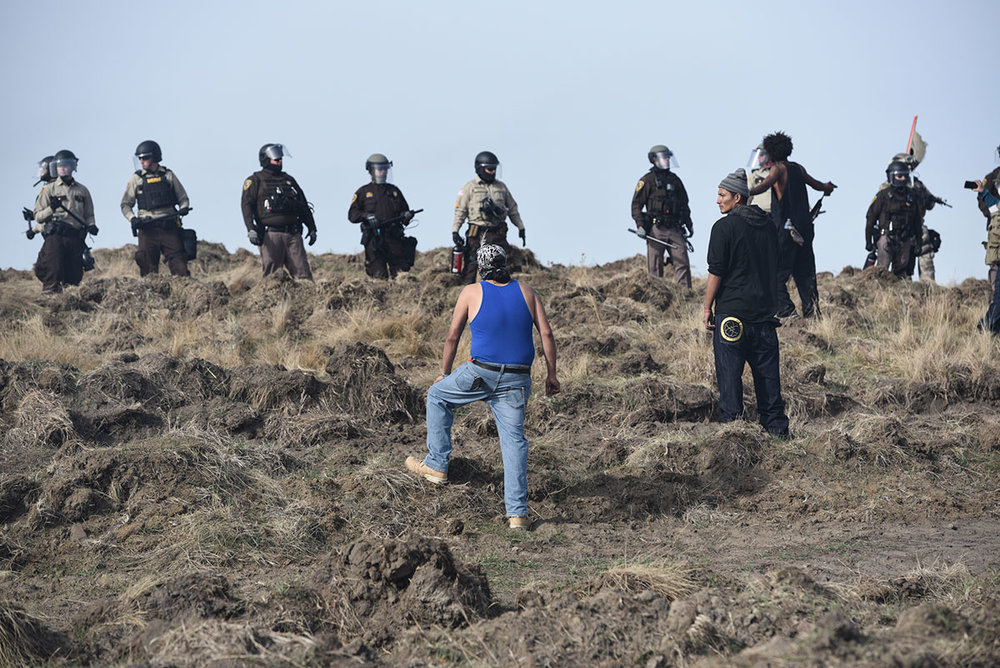 Protesters confront police over ground the Lakota tribe considers as sacred burial grounds but which the Dakota Access oil company dug up earlier this year. [Jason Patinkin/Al Jazeera]