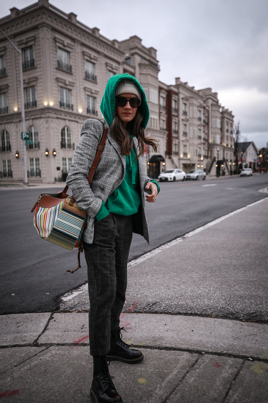 Nathalie Martin wearing plaid blazerk from Zara, green Isabel Marant hoodie, Aritzia wool Chambery pant, Doc Marten boots, striped Loewe hammock bag, Acne Studios ivory Pansy face beanie, woahstyle.com_4766.jpg