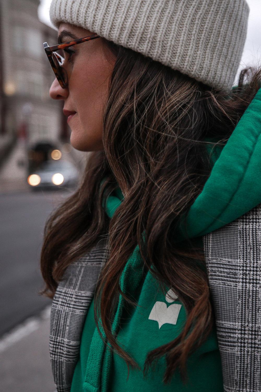 Nathalie Martin wearing plaid blazerk from Zara, green Isabel Marant hoodie, Aritzia wool Chambery pant, Doc Marten boots, striped Loewe hammock bag, Acne Studios ivory Pansy face beanie, woahstyle.com_4792.jpg