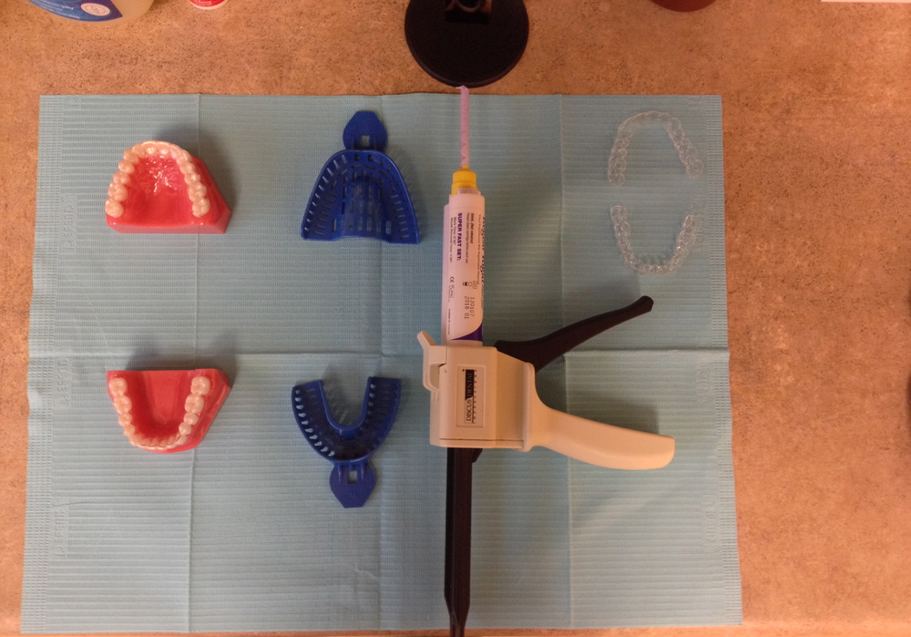 "From left to right: We use the blue trays to take a quick impression of your teeth, followed by a ""bite impression"" using the purple material in the applicator gun (called Regisil). After invisalign receives and processes your impressions, we receive your custom trays (pictured far right)."