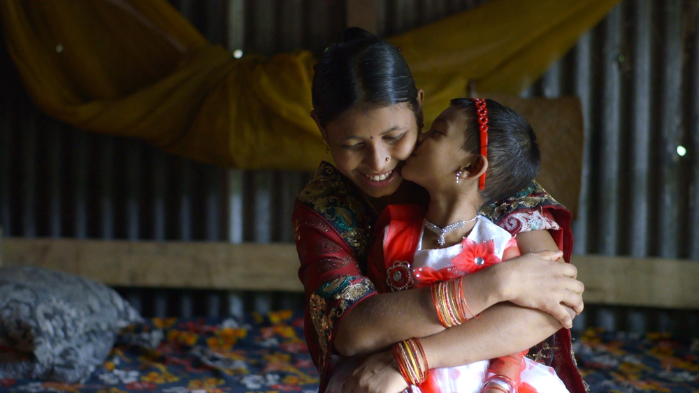Shima Akhter hugs her daughter, Nadia, on the morning that she has to leave her with her family in a village in the countryside. She will only see her twice a year, since Shima must remain in Dhaka to work at a garment factory. Image Source: The True Cost.