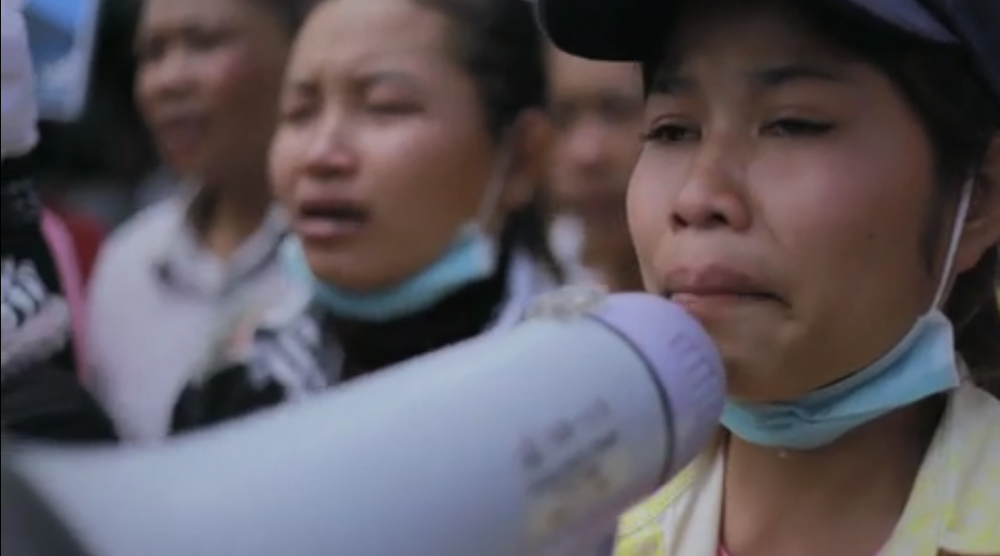 A Cambodian woman demands living wages through her tears during a protest in Cambodia. She works at a factory that produces clothing for H&M and Walmart. Image Source: The True Cost.