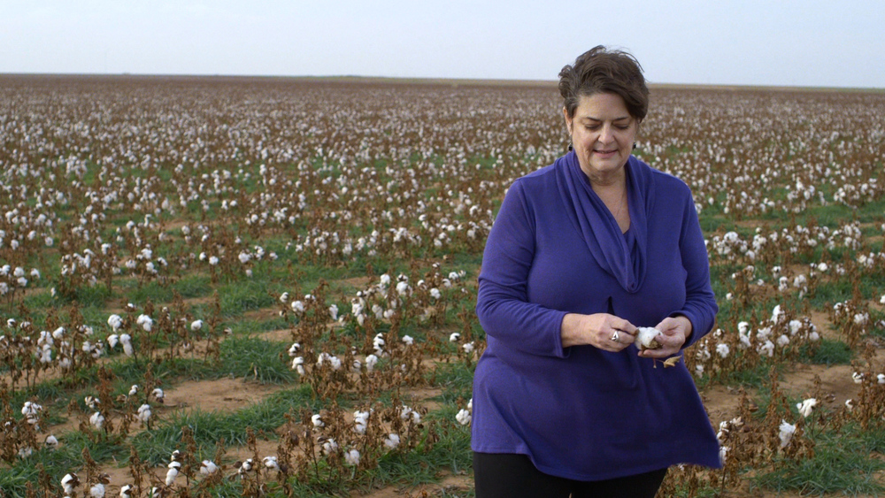 Larhea Pepper walks in her organic cotton field. Her husband died of a brain tumor which was caused by his close contact with chemical pesticides. Image Source: The True Cost.