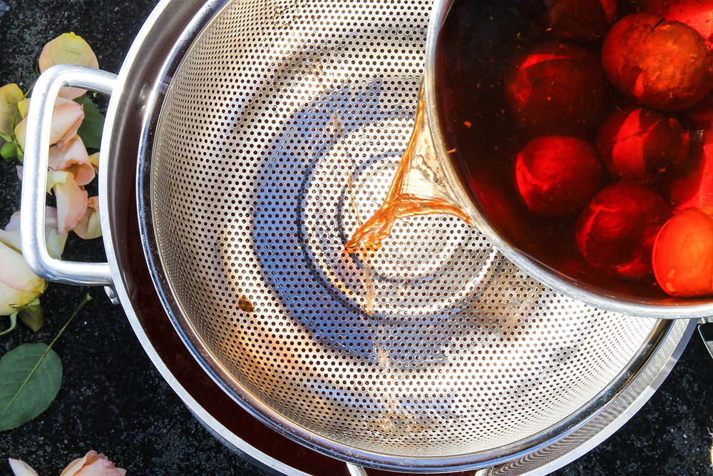 Ruby red dye extract being strained into the large dye bath.