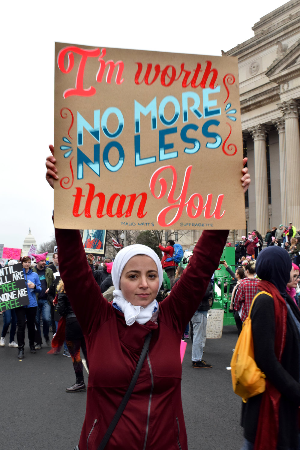 "A woman holding a sign reading ""I'm worth no more, no less than you"" at the Women's March on Washington"