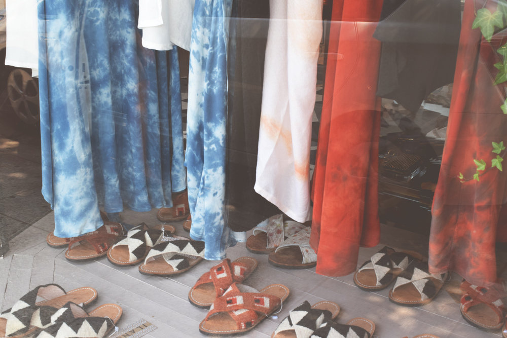 image of sustainable, ethical clothing and shoes in a boutique window