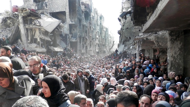 Photo taken in Damascus on January 31, 2014 of Syrians lining up for food and supplies. Released by the United Nations Relief and Works Agency.