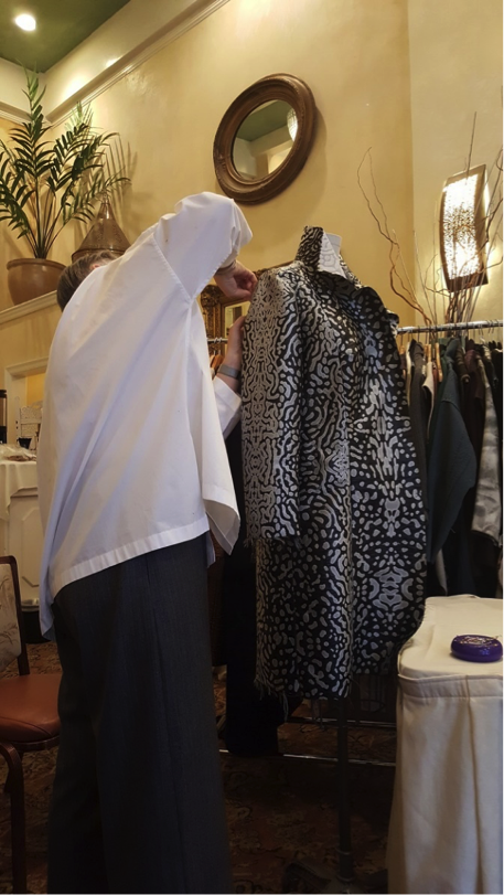 Kathryn sets the sleeve into Shams' coat.