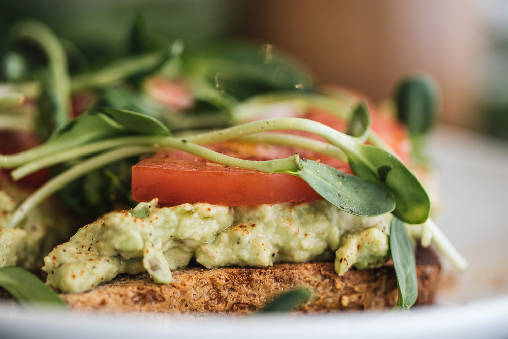 Dukka Avocado Toast on Ezekiel bread: avocado, dukka spice, crushed almonds, tomato, and sprouts with a drizzle of olive oil