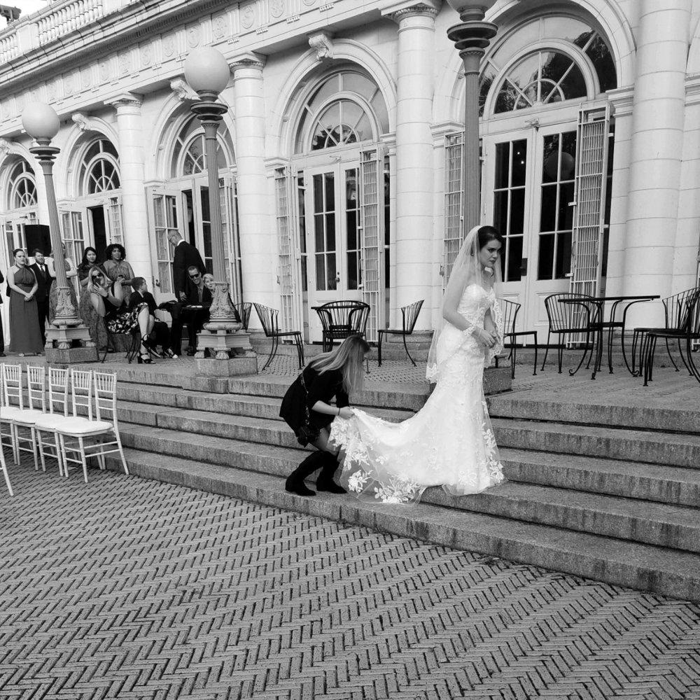 BTS-Maura+Kyle-Prospect Park Boathouse Wedding- Photographer fixing Bride's Dress.jpg
