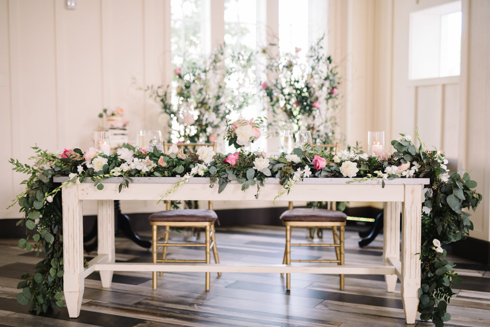 Garland - Instead of having 1 or 2 large centerpiece arrangements, cascade floral garland down the center of the table for a simple but beautiful impact. You can keep it plain with all greenery, add pops of light with low candles alongside it, or intertwine your favorite flowers between the vines.