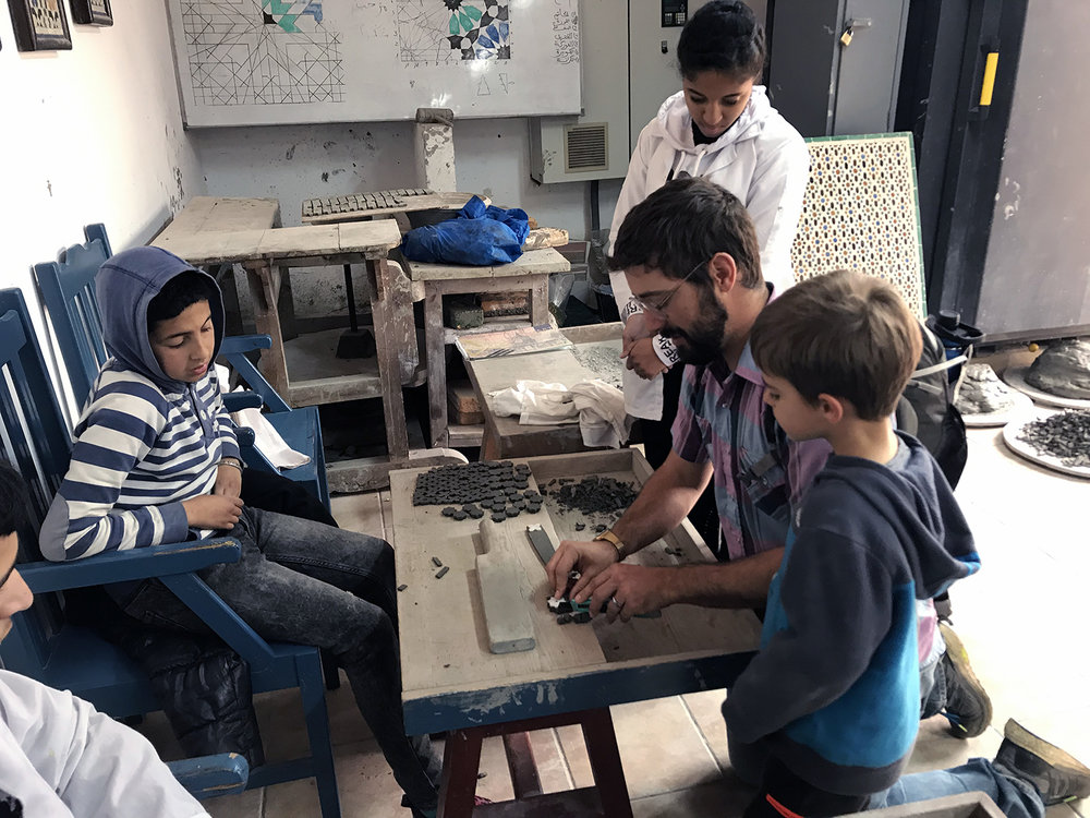 A young tiler teaches an older Tyler how to be a tiler