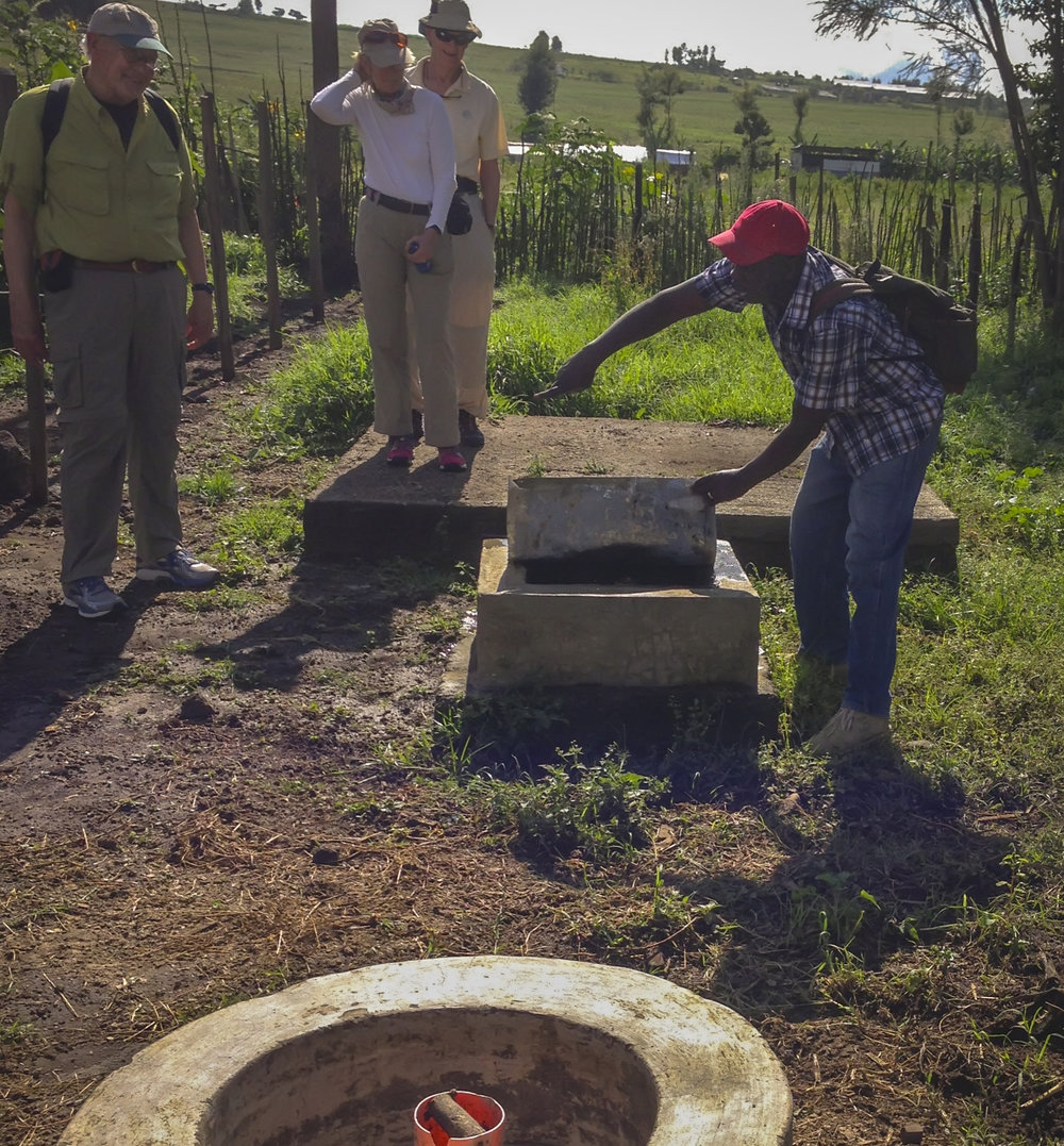 Josphat demonstrates the fixed-dome biogas digester