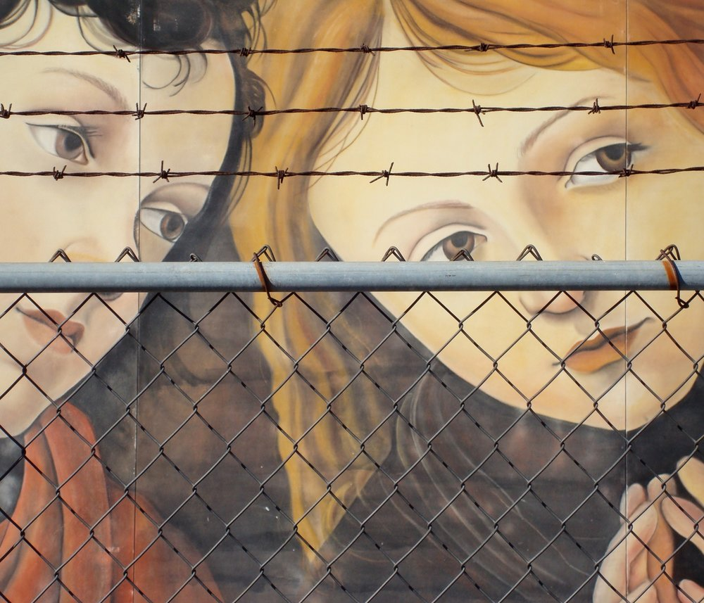 This photo of street art was taken in San Diego. The image of the sweet girls is definitely at odds with the barbwire fence.