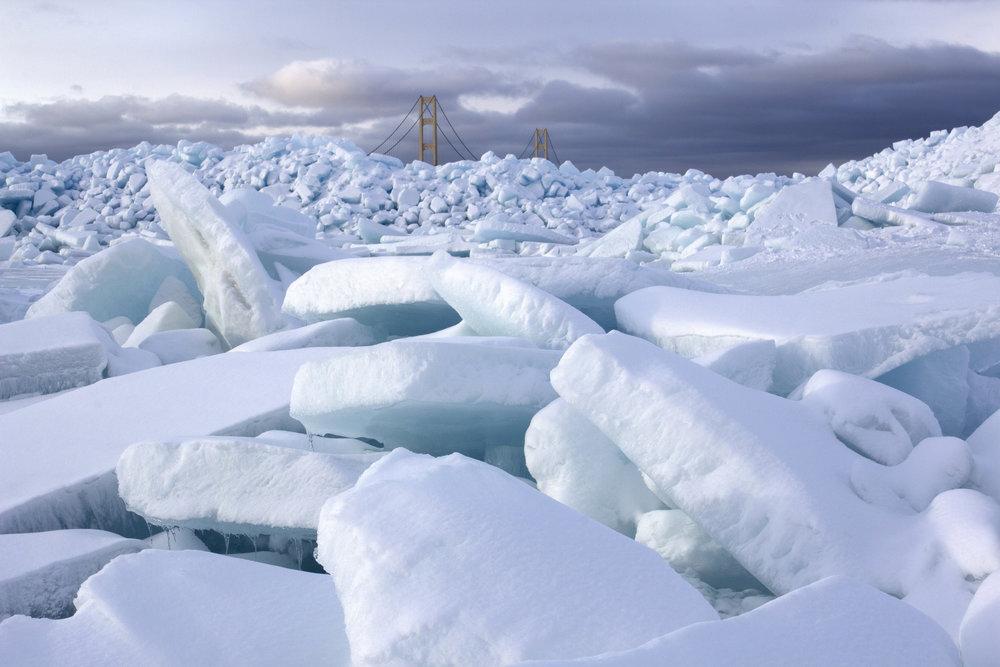Mackinac Bridge peaking over giant piles of blue ice on the Straights of Mackinac.
