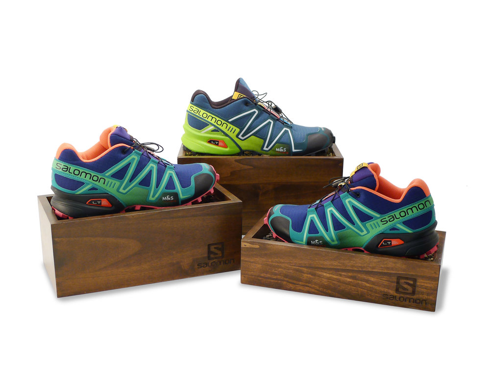 Salomon Trail Shoe Risers, featuring natural elements: rocks, moss, simulated wood chips