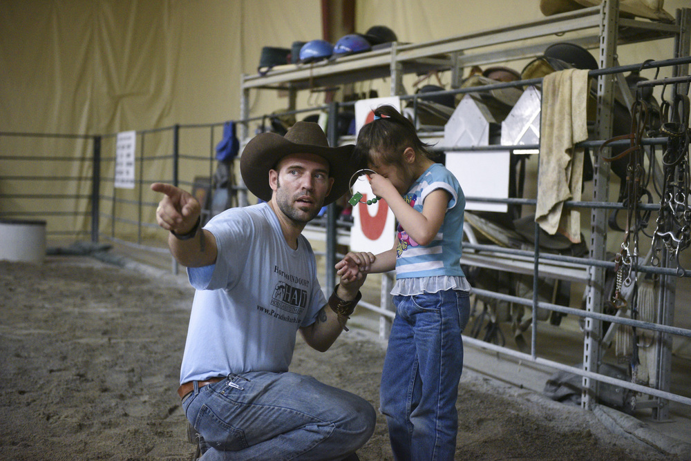 Horse Assisted Therapy (HAT) program participant Sophia Nola Hudig, right, struggles to follow Paul Roger's instruction to put an item away at Paradise Ranch in Las Vegas, Wednesday, June 3, 2015. Hudig, who has been diagnosed with autism and ADHD, has been part of the Ranch's HAT program on a scholarship for three years.(Jason Ogulnik/Las Vegas Review-Journal)
