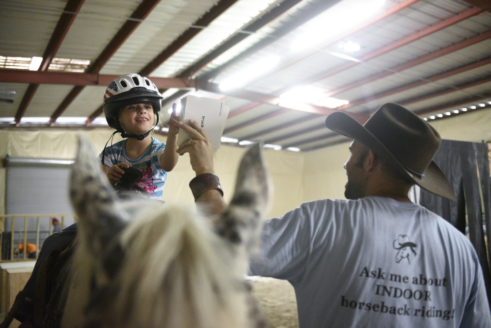 Horse Assisted Therapy (HAT) participant, Sophia Nola Hudig, 7, left, and Paul Rogers, owner of Paradise Ranch in Las Vegas, describe emotions that are shown in a series of photographs, Wednesday, June 3, 2015. Hudig, who has been diagnosed with autism and ADHD, has been part of the Ranch's HAT program on a scholarship for three years. (Jason Ogulnik/Las Vegas Review-Journal)