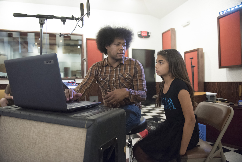 """Diego Cano, left, and Ava Thrasher, 10, review Thrasher's lyrics to her song """"remember"""" prior to recording at National Southwestern Recording in Las Vegas, Thursday, July 16, 2015.(Jason Ogulnik/Las Vegas Review-Journal)"""