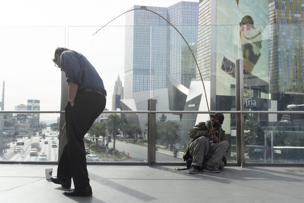 A man, who did not want to give his name, left, places coins into Clarence Witzel's panhandling cup on the pedestrian overpass at South Las Vegas Boulevard and West Harmon Avenue in Las Vegas Thursday, Jan. 21, 2016. Witzel's panhandling set up is meant to mimic a fishing rod. Jason Ogulnik/Las Vegas Review-Journal