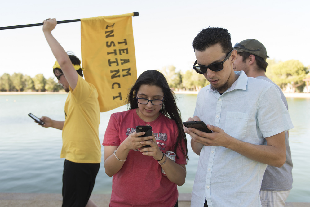 Jennifer Soto, center, and Joao Silva, right, play Pokemon Go at Sunset Park in Las Vegas Sunday, July 10, 2016. Eddy Wojdan of team Instinct waves a flag in the background. More than 2,000 Pokemon Go gamers came to the event. Jason Ogulnik/Las Vegas Review-Journal