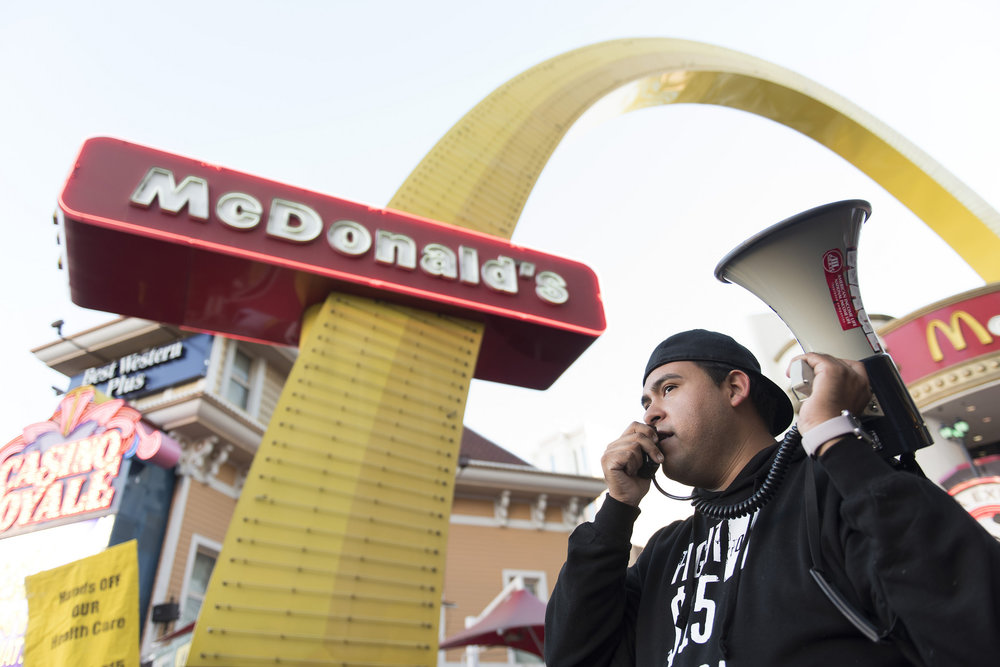 Jose Macias speaks to demonstrators gathered at a Fight for $15 protest outside of the McDonald's restaurant at Harrah's hotel-casino in Las Vegas, Tuesday, Nov. 29, 2016. Demonstrators in more than 300 cities nationwide gather at fast-food restaurants to demand minimum wage be raised to $15/hour.