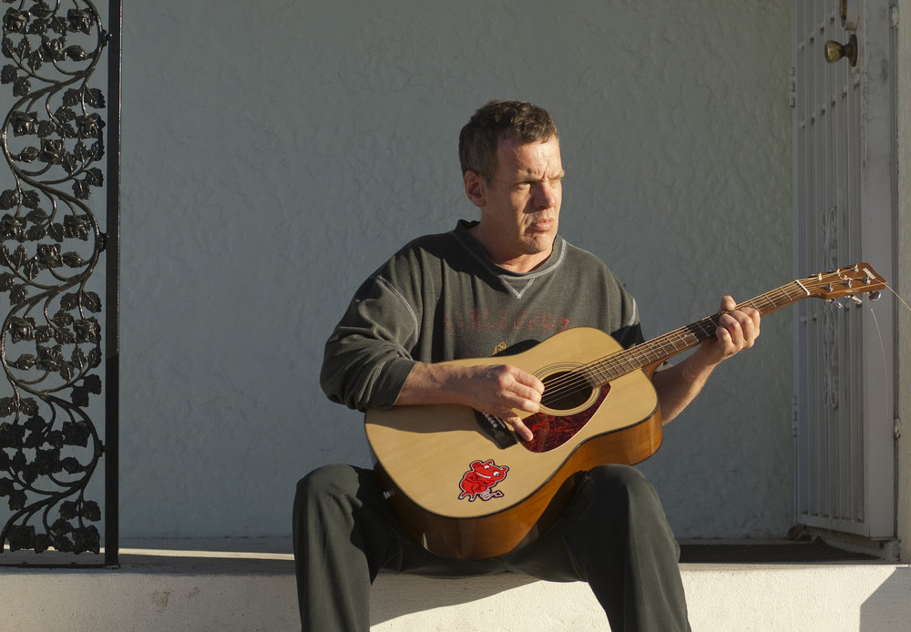 Eddie Kenny plays guitar on the front steps of his downtown Las Vegas home, Sunday, Jan. 25, 2015.
