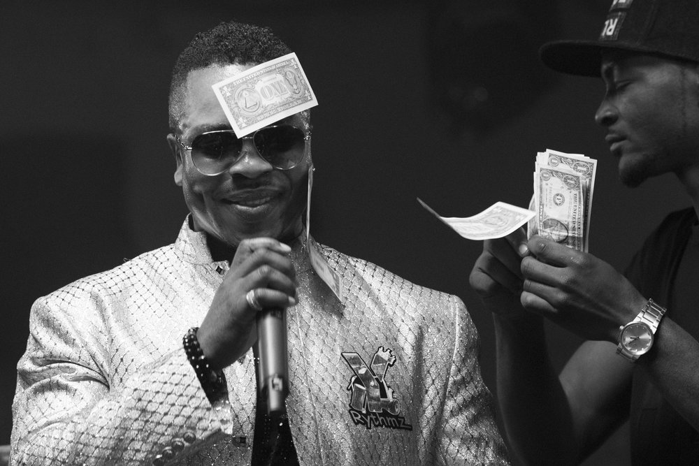 Money sticks to Yinka Rythmz's sweaty forehead as he performs during the I Am Somebody Las Vegas 2.0 show at Mia's Banquet Hall in Las Vegas, Saturday, Dec. 17, 2016.