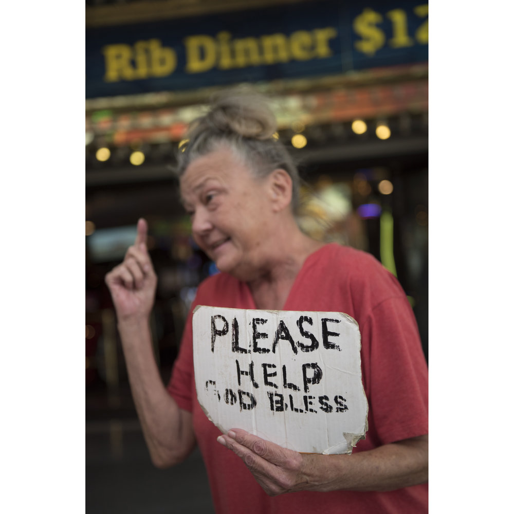 A panhandling woman holds a sign as she speaks with Merideth Spriggs, founder of Caridad, out of frame, at Fremont Street Experience in Las Vegas, Wednesday, Aug. 24, 2016. Caridad is an nonprofit organization which connects the homeless to resources. Jason Ogulnik/Las Vegas Review-Journal